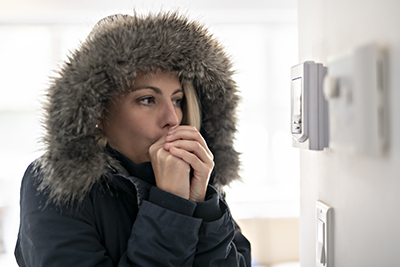 Manasquan heating repair, cold woman in winter coat with furry hood standing in front of thermostat