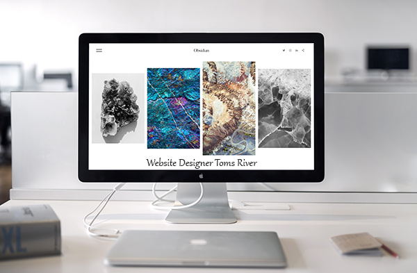 Website designer in Toms River work displayed on Apple monitor on white desk in front of blurred white background
